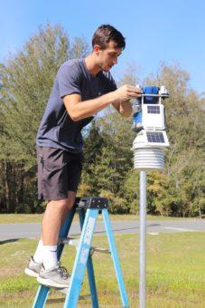 boy next to WeatherSTEM weather station