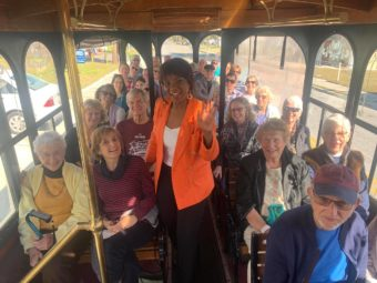 Black woman waving in the aisle of a sightseeing tour trolley, with the seats full of passengers.