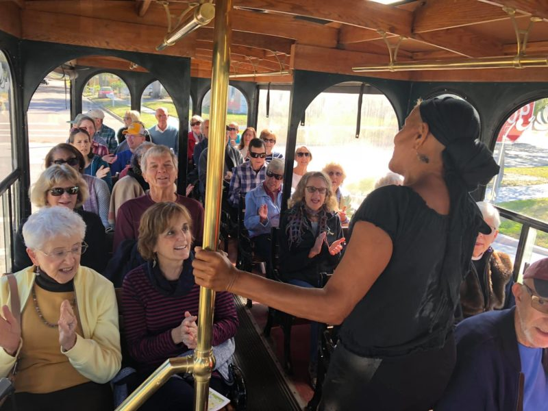 Black woman speaking in the aisle of a sightseeing tour trolley, with the seats full of passengers.