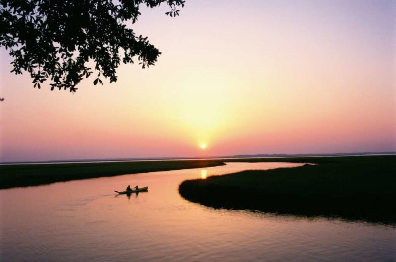 sunset over amelia beach with kayak in water