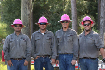 Group of workers outside wearing pink hard hats.
