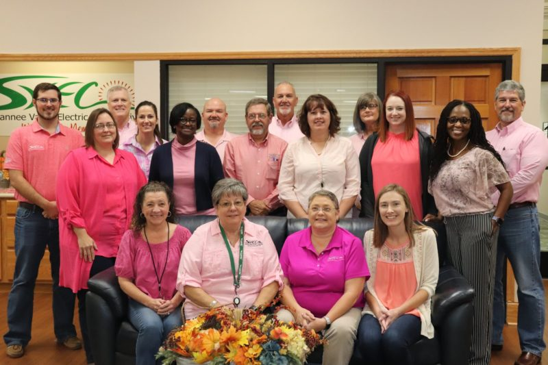 Large group of people on and behind a couch, all wearing pink shirts.