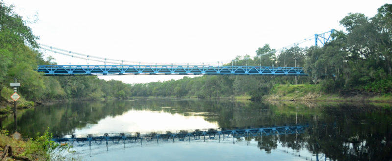 A blue bridge passes over a river, connecting tree lined banks