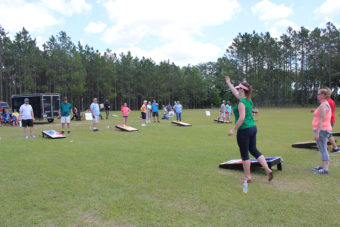 woman throwing bag for charity cornhole tournament