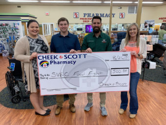 members from Cheek & Scott Pharmacy holding large check for the SVEC food fight