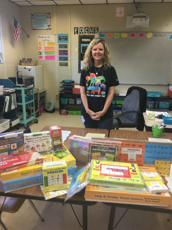 Woman in front of a table filled with with boardgames.