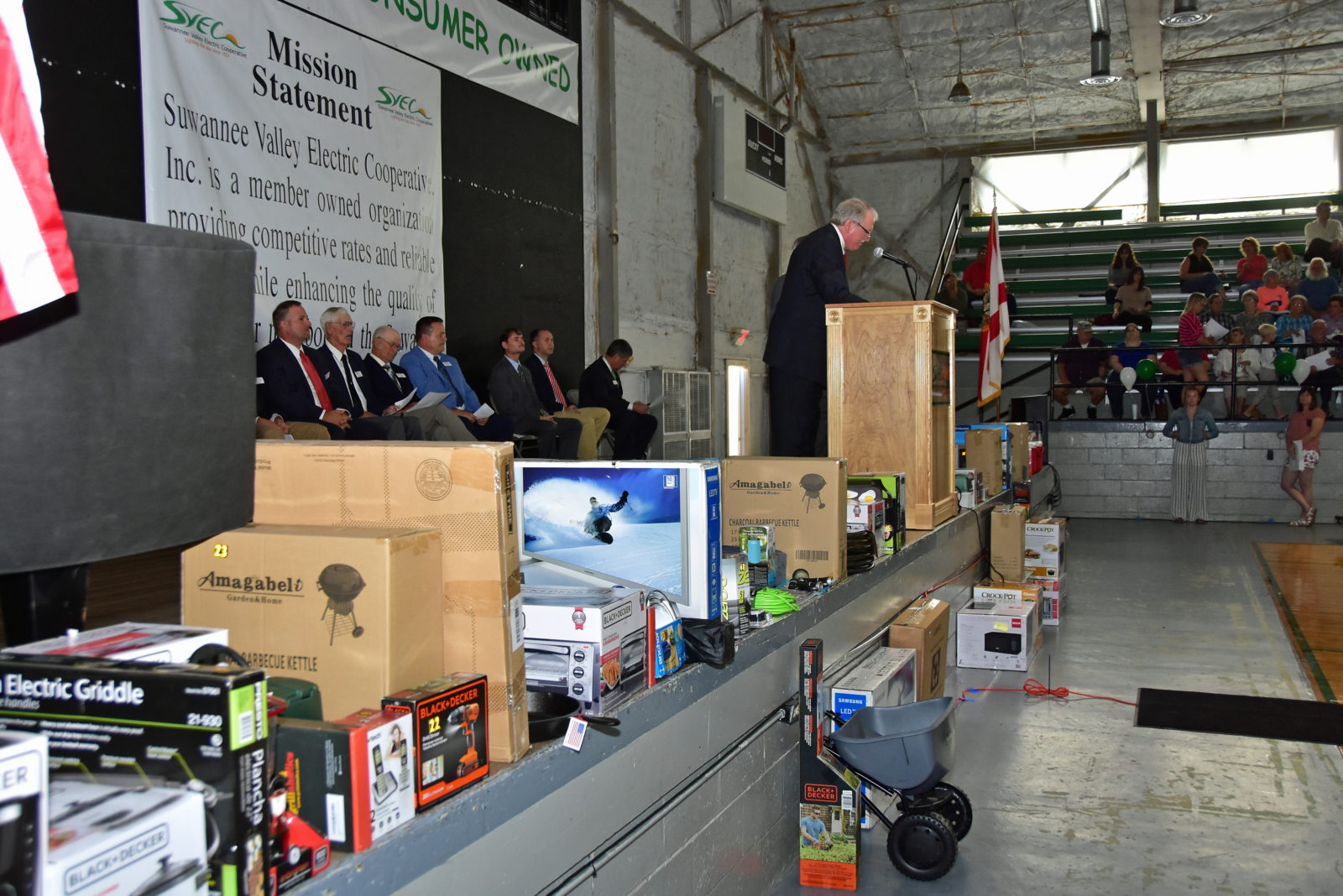 A man speaking at podium with the board of directors sitting behind him. Various door prizes, including a TV and a grill, are sitting on stage. A banner behind him contains the SVEC logo and reads: Mission Statement. Suwannee Valley Electric Cooperative, Inc. is a member owned organization providing competitive rates and reliable service while…