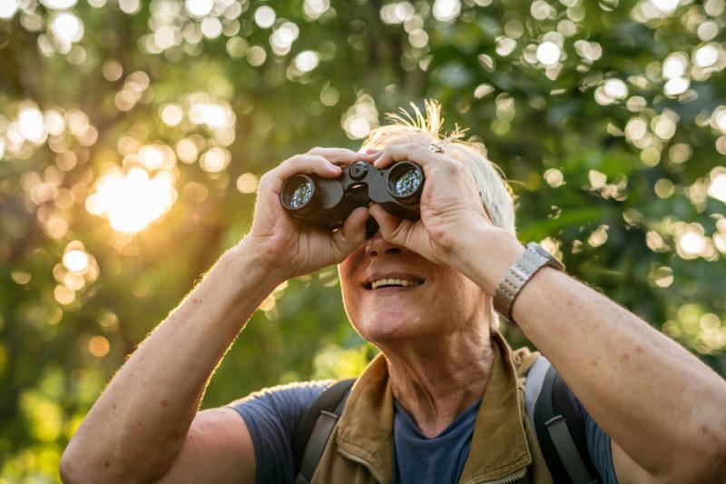 elderly man watching birds through binoculars