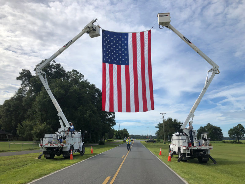 two bucket trucks holding up American flag