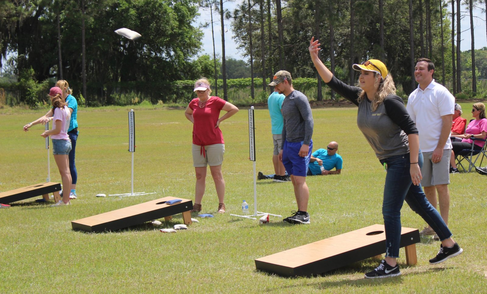 people participate in a cornhole tournament