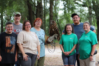 Group of people standing in a forest with a woman holding an owl.