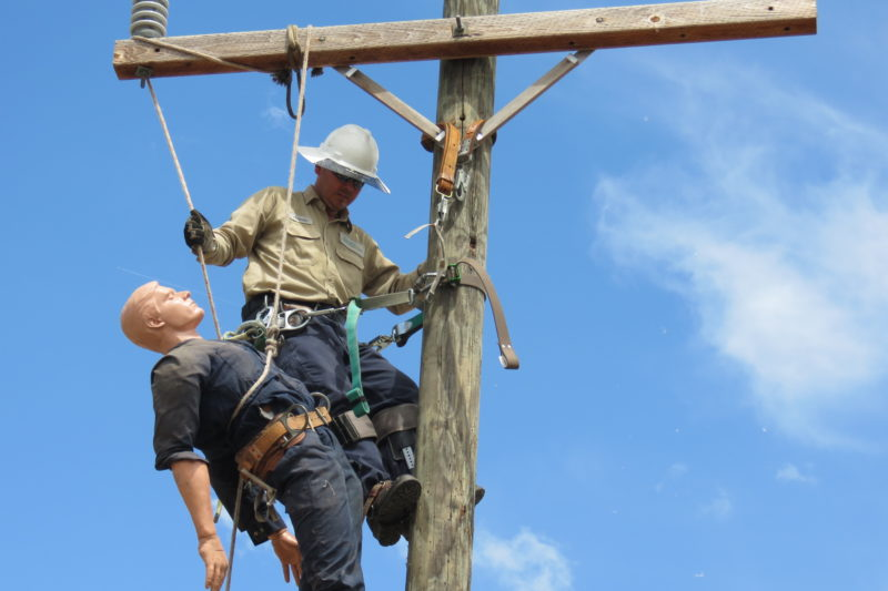 Lineworker practices a rescue exercise with a dummy