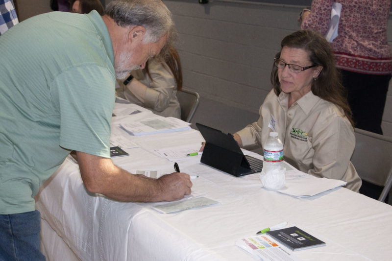 Employee Page watches a member fill out a form on a table in front of her at the annual meeting