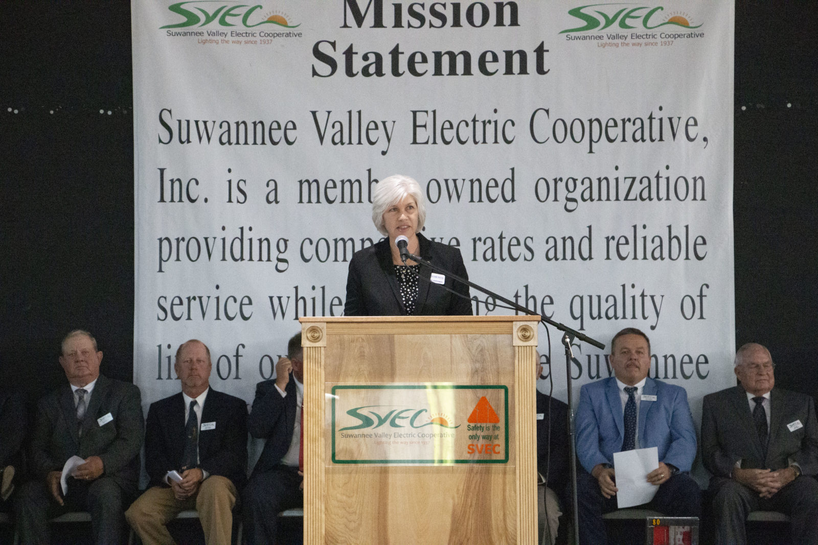 General Manager Lisa Johnson speaking at a podium with board members seated behind her. A banner behind her contains the SVEC logo and reads: Mission Statement. Suwannee Valley Electric Cooperative, Inc. is a member owned organization providing competitive rates and reliable service while…