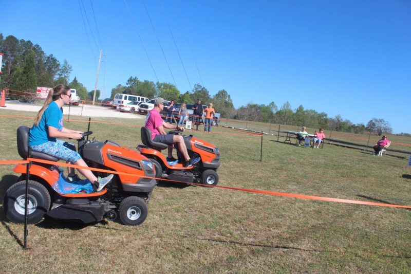 people riding lawn mowers