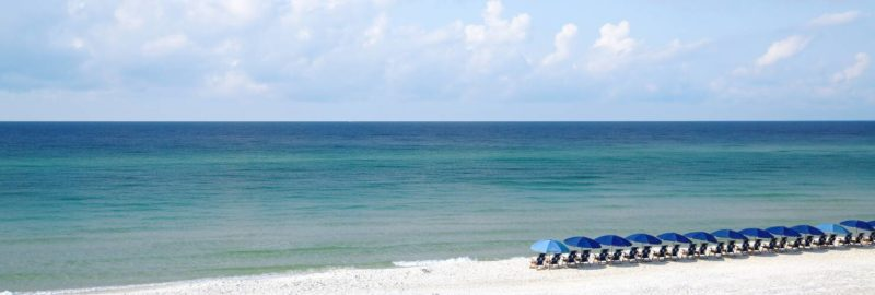 Row of people sitting in lounge chairs under umbrellas on a beach
