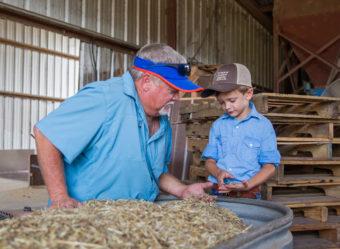 farmer with young boy near hay