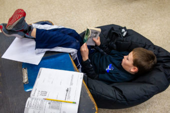 young boy reading on floor