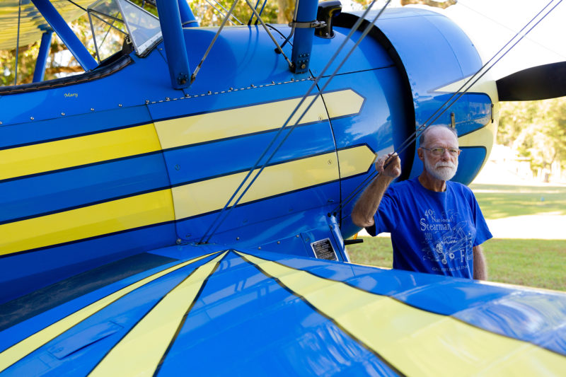 man standing next to blue plane with yellow stripes