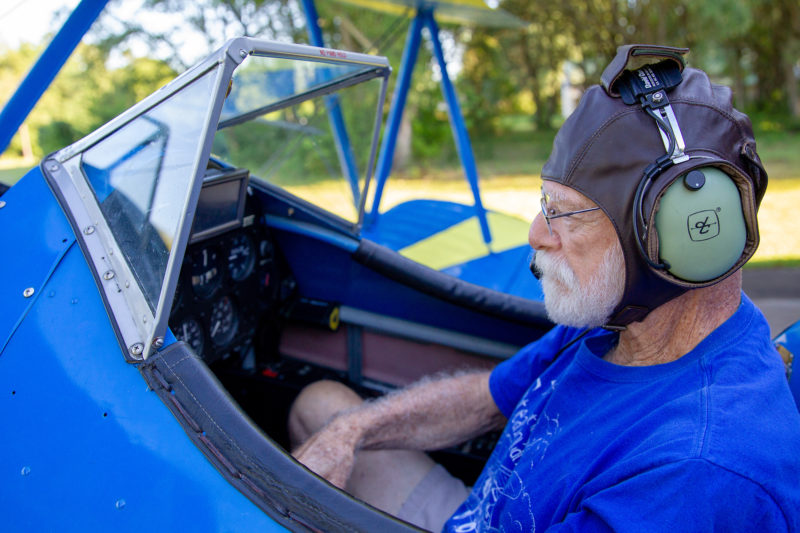 man in cockpit of small blue plane