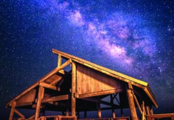 blue starry sky above cabin