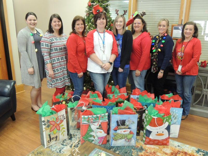 SVEC employees standing in front of a collection of gift bags