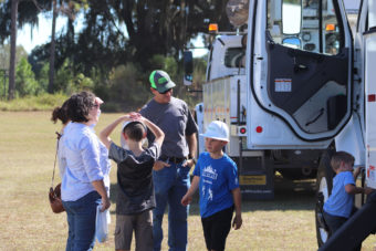 Man with group of kids in hard hats next to a truck.