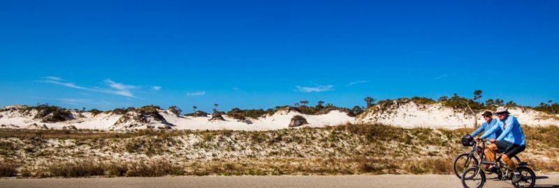 Couple biking on a path near dunes