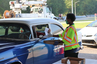 Woman handing a slip of paper to a man in a car.