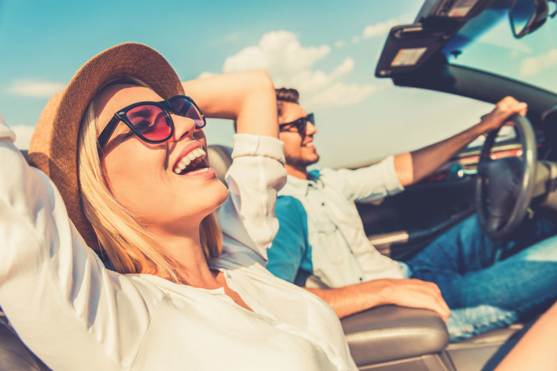 man and woman in car with top down driving