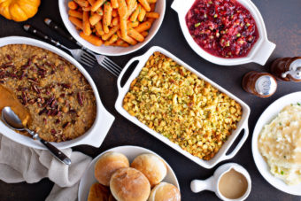 Variety of Thanksgiving sides on the dinner table, carrots, mashed potatoes, sweet potato casserole and stuffing