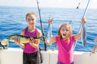 two little girls on boat holding fish