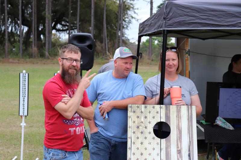 men watching cornhole tournament