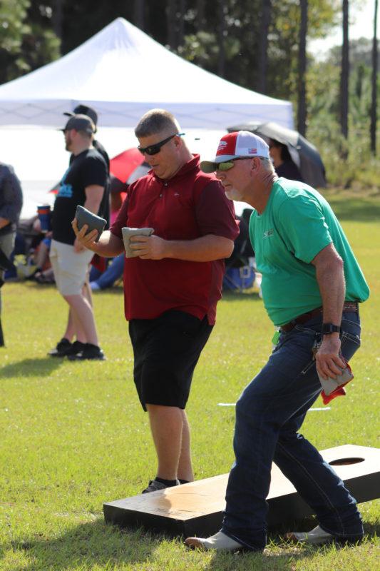 men playing at cornhole tournament
