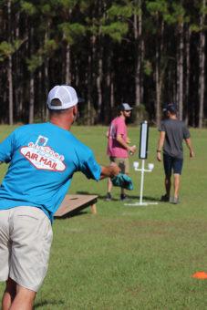 man throwing bag in cornhole tournament