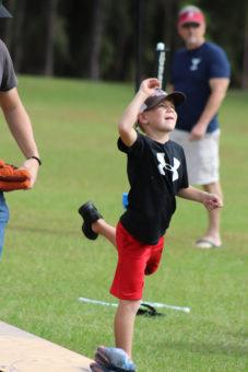 small boy throwing cornhole