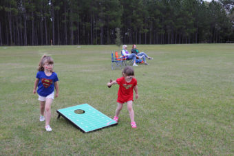 young girl playing at the cornhole tournament