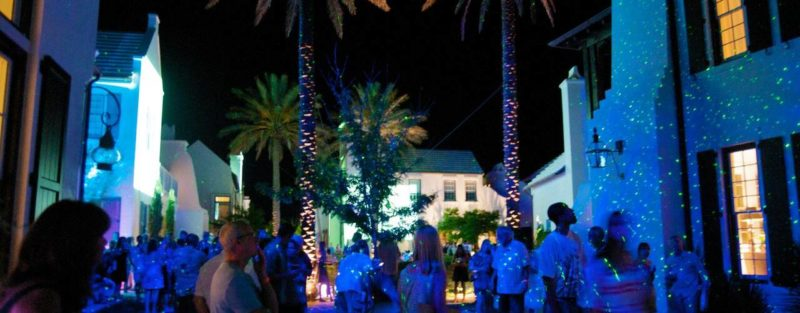 People outside town at night with lights on the buildings and palm trees