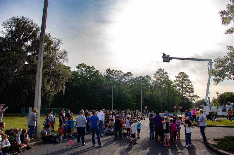 kids gathered around bucket truck