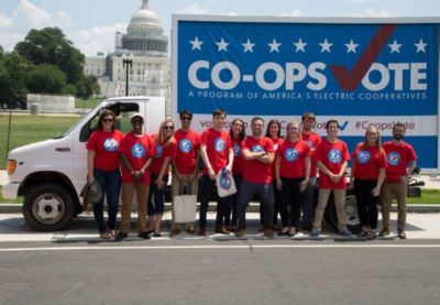 """Large group of people standing in front of a sign that says """"Co-ops Vote"""""""