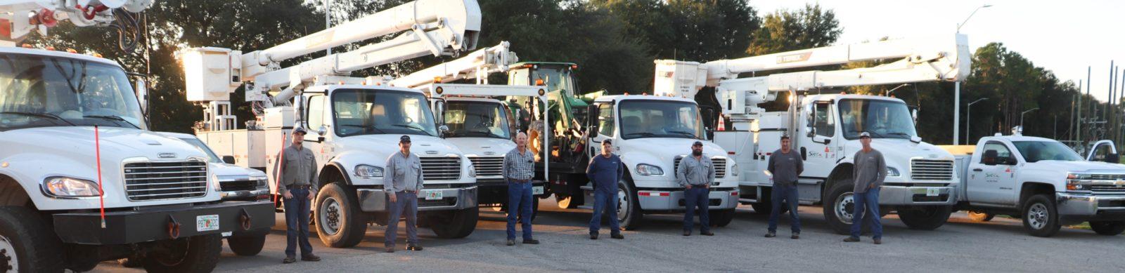 linemen standing in front of bucket trucks