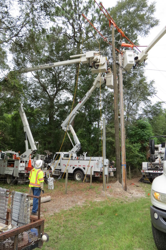 linemen with trucks and power poles