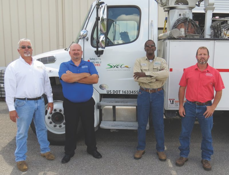 4 SVEC employees who are veterans stand in front of a truck