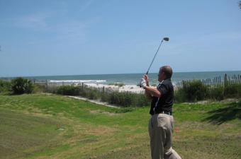 man swinging club at golf course