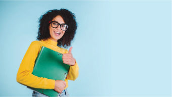 woman wearing glasses holding notebook and smiling