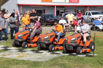group of people in lawn mowers at start of race