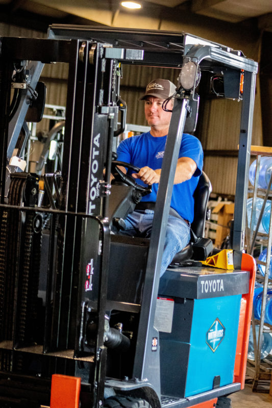 man using forklift in warehouse