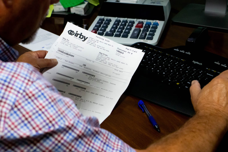 man looking at invoices at desk