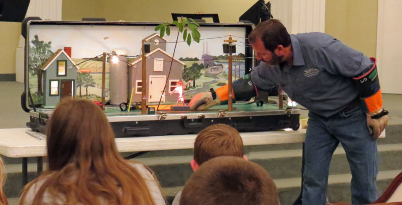 lineman giving safety demonstration to kids