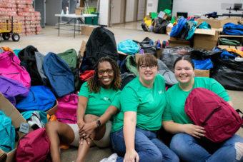 volunteers smiling next to backpacks